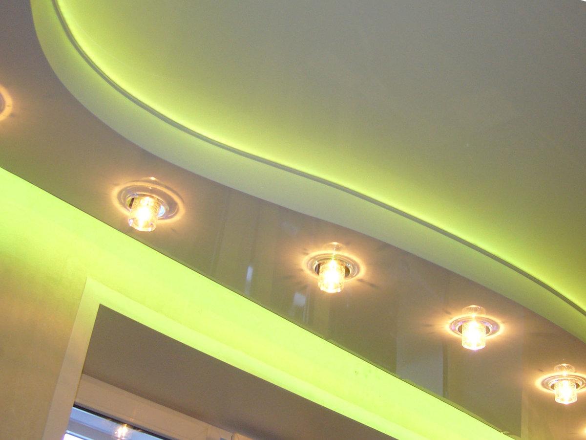 Криволинейный глянцевый потолок с множеством светильников яркого света