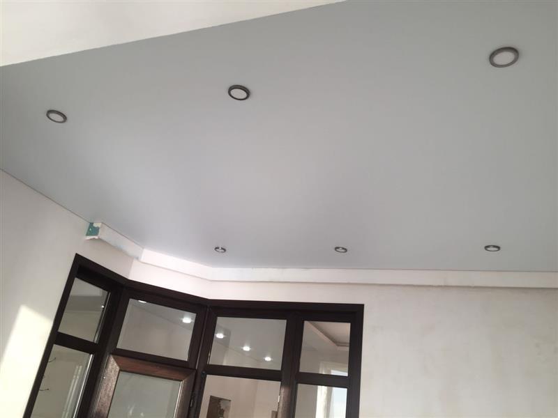 Бесшовный потолок в зале с встроенным освещением и плинтусом, высота потолка  2,2м